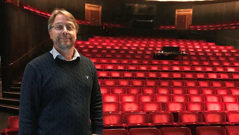 En man framför en massa stolar i en teatersalong