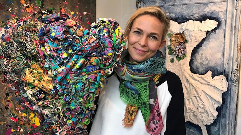 En kvinna omgiven av färgsprakande konstverk gjorda av skräp.