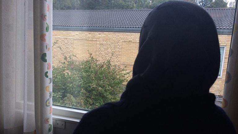 kvinna med slöja vid fönster