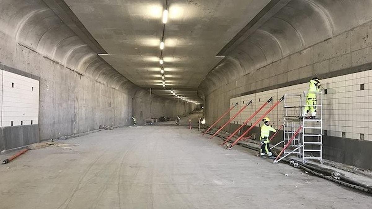 Personer arbetar med att sätta kakel på väggarna inuti den ännu inte färdigbyggda Marieholmstunneln.