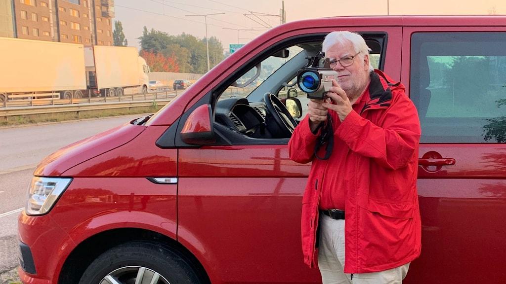 Man i röd jacka framför en röd bil. Stor och mäter hastigheten med en laserkamera.