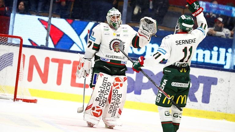 Hockeymålvakt och spelare gör segergest.