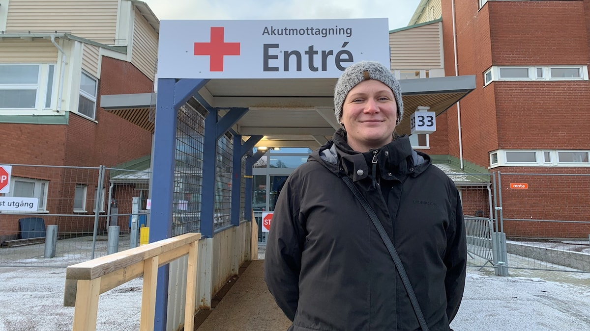Kvinna framför Mölndals sjukhus med skylten Akutmottagning entré.