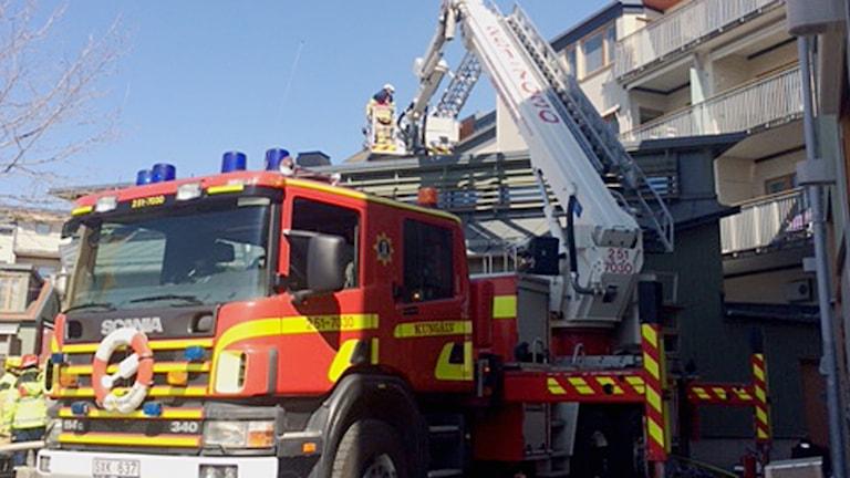 en brandman hissas upp i brandbilens kran.