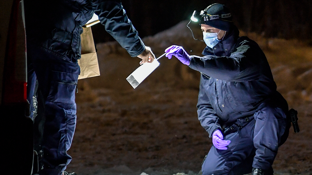 A masked person putting something into a plastic bag held by another person.