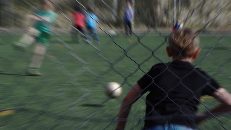 Små pojkar spelar fotboll.