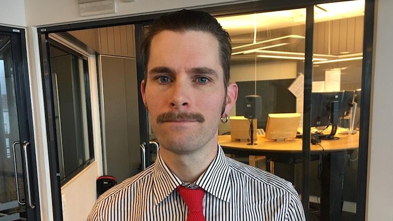En man med brunt hår och mustasch.