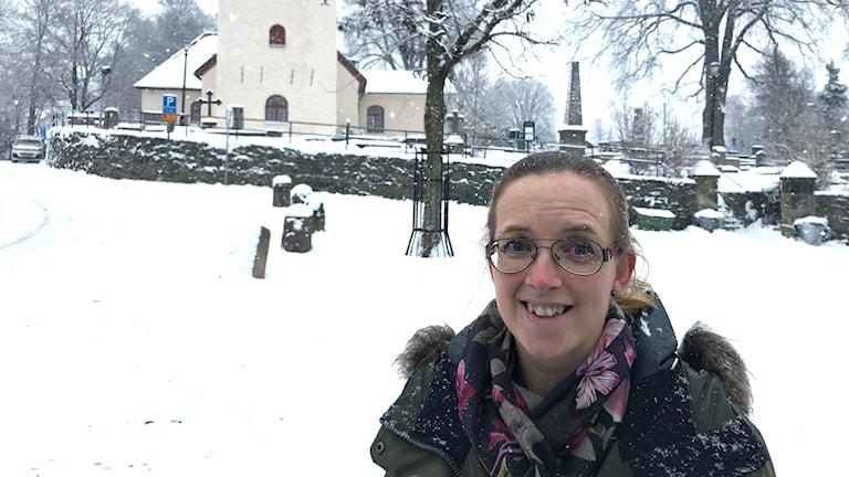 En kvinna framför en kyrka