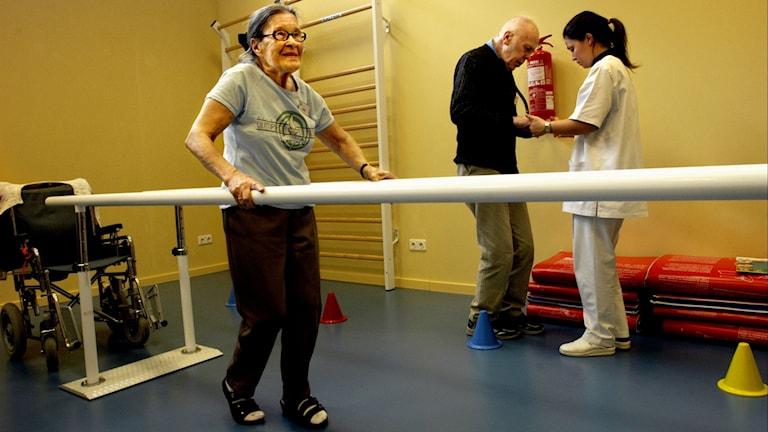 Gammal kvinna tränar gång mellan två räcken