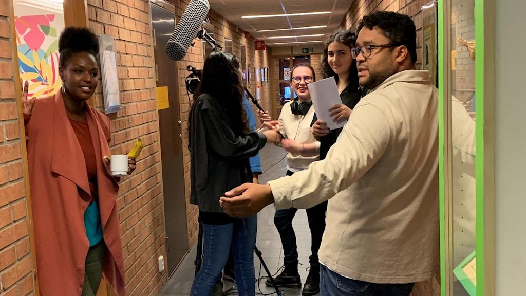I en korridor står 5 personer som har en kamera och mikrofon