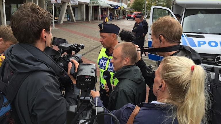Polis omgiven av reportrar