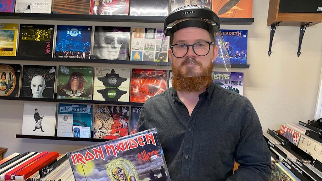 Man med skägg, visir och en heavy metal-LP i handen
