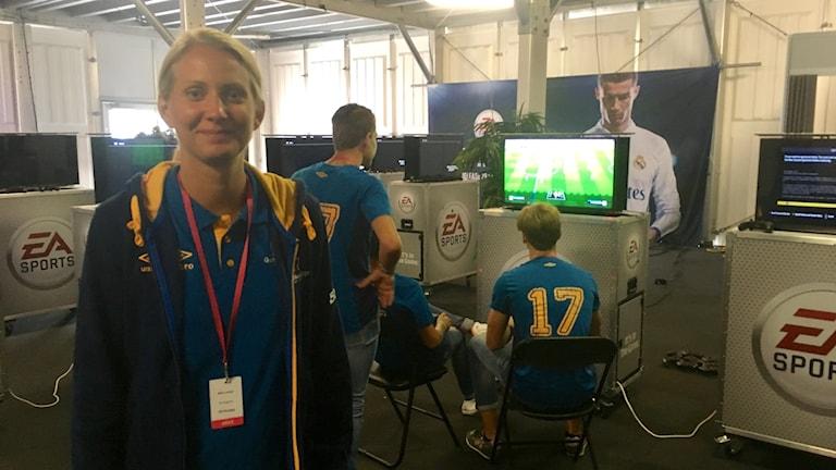 Kvinna i förgrunden och killar som spelar dataspel i bakgrunden