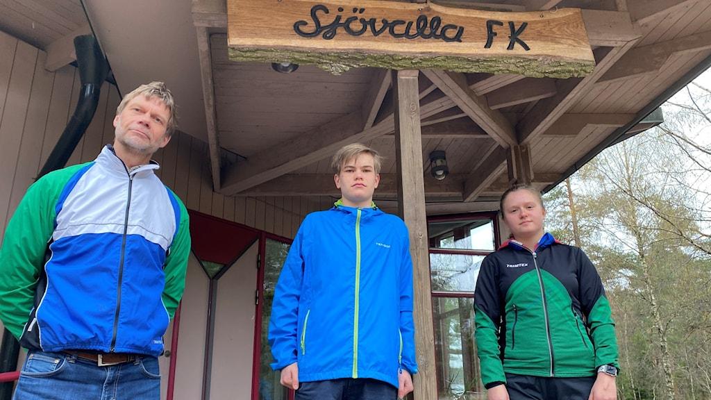 Tre personer i träningsoveraller i grönt och blått framför klubbstuga.