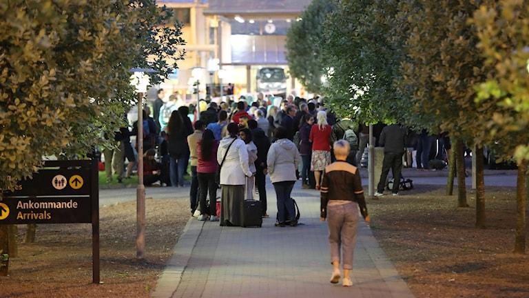 Människor väntar utanför den avspärrade flygplatsen.