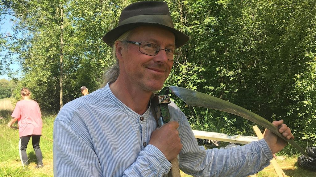 en bild på Mats Rosengren, med hatt på huvudet och en sylvass lie i handen. I bakgrunden syns personer öva på att använda lien