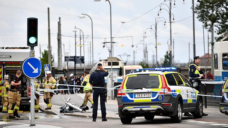 En polis och en polisbil samt personal från räddningstjänsten.
