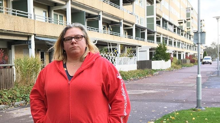 En kvinna med askblont hår och glasögon, klädd i en röd luvtröja. Hon står framför ett hyreshus.