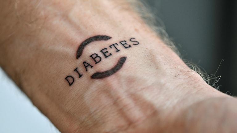 """En man har tatuerat ordet """"DIABETES"""" på insidan av handleden."""