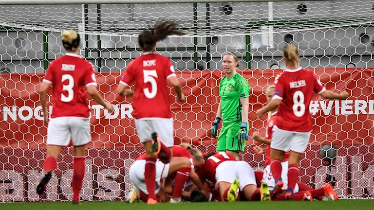 Tjejer i röda och vita fotbollsdräkter jublar efter ett mål.