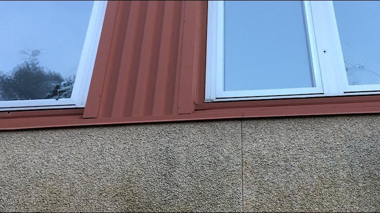 Skotthål i två fönster i bottenvåningen på ett flerfamiljshus i Biskopsgården