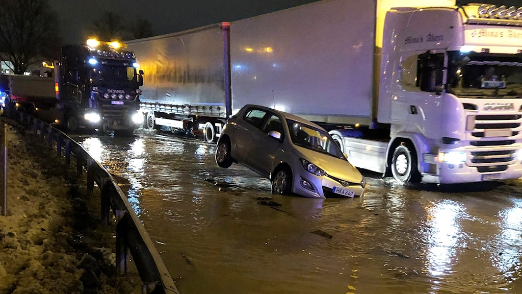 en bil har kört fast i ett hål mitt i vägen och vatten har läckt ut över vägen