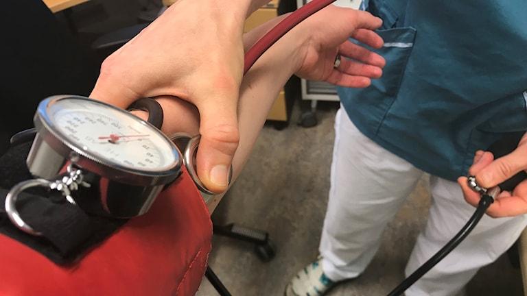Armar och händer, närbild på ett blodtryckstest