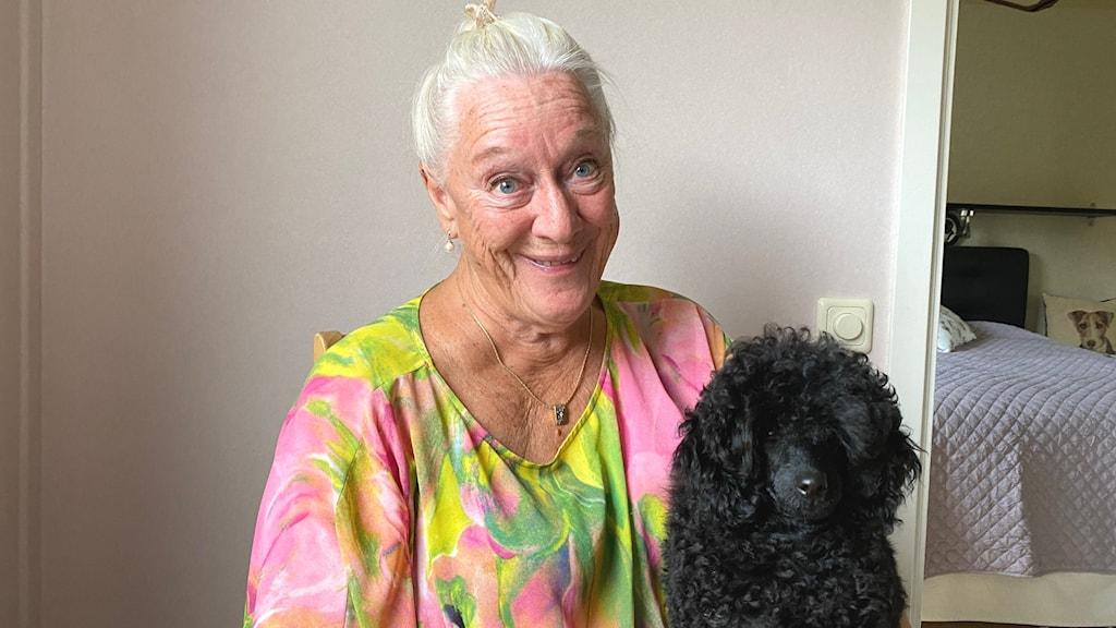 Kvinna ler mot kameran och har en hund i knäet.