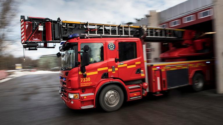 En brandbil kör ut från brandstation.