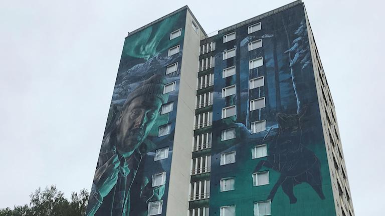 En väggmålning täcker fasaden på ett högt flerfamiljshus.