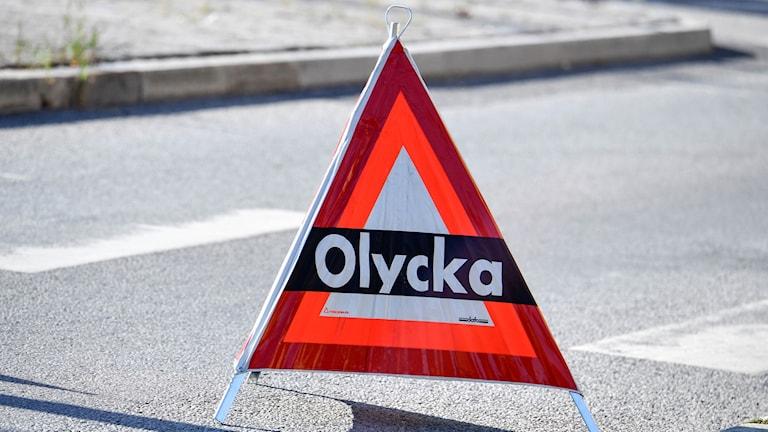 """En varningstriangel på asfalt med texten """"Olycka""""."""