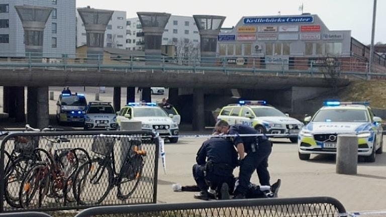 poliser håller en man på marken