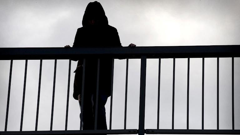 Fotot visar en siluett av en människa på en bro