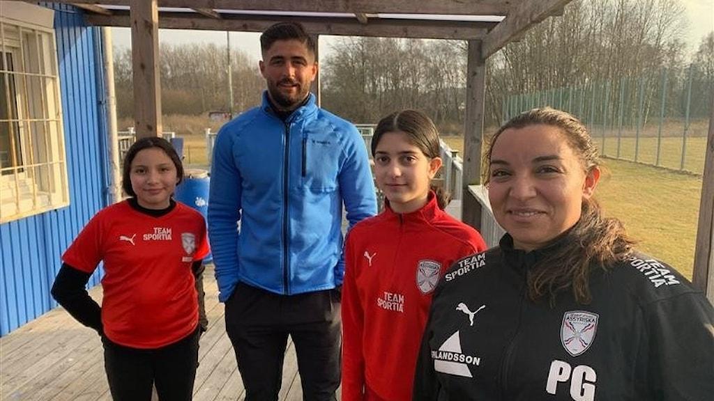 På bilden syns två flickor i röda träningströjor, En lång man i blå tröja och en kvinna lita mer i förgrunden i svart träningsjacka. I bakgrunden en fotbollsplan i blekt eftermiddagskjus.