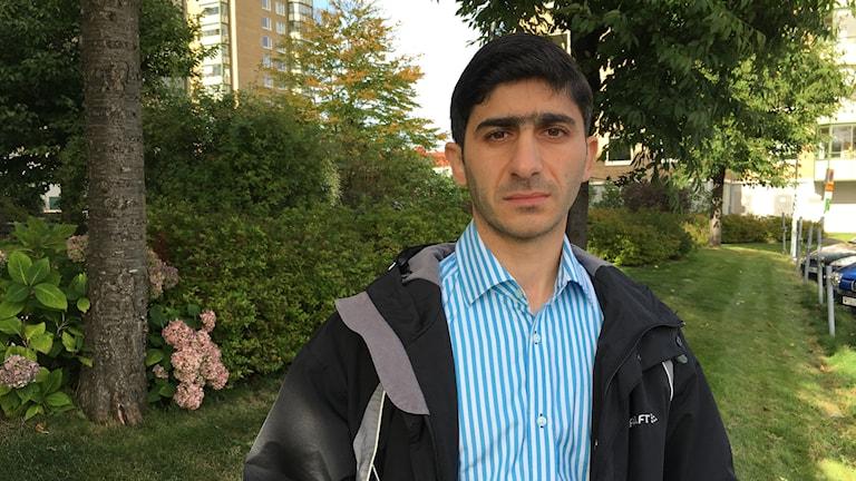 Mohammed Bader från Aleppo står framför en häck.