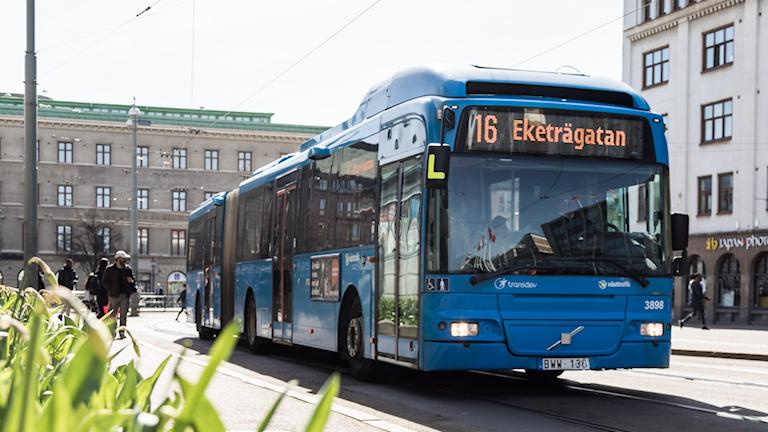 en blå buss kör på en gata.