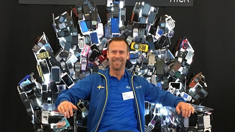 Joel Lindqvist ATEA sitter i throne-stol gjord av gamla mobiler