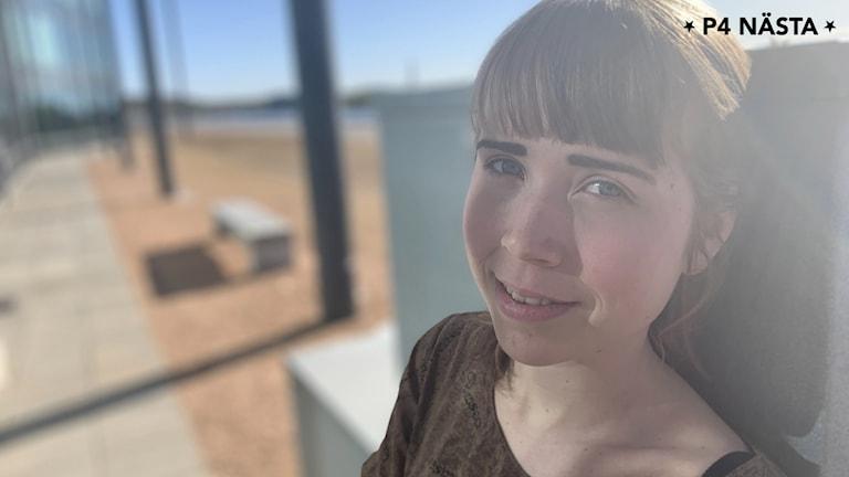 Maja lutar huvudet mot ett betongstaket. Hon tittar rakt in i kameran och ler lite. Brunt hår med rak, kort lugg.