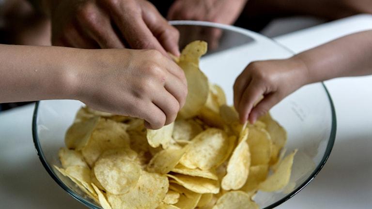 Händer som tar chips ur en skål.
