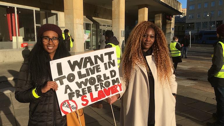 Lola Ahmed och Fiona Rydström med plakat mot slavhandel