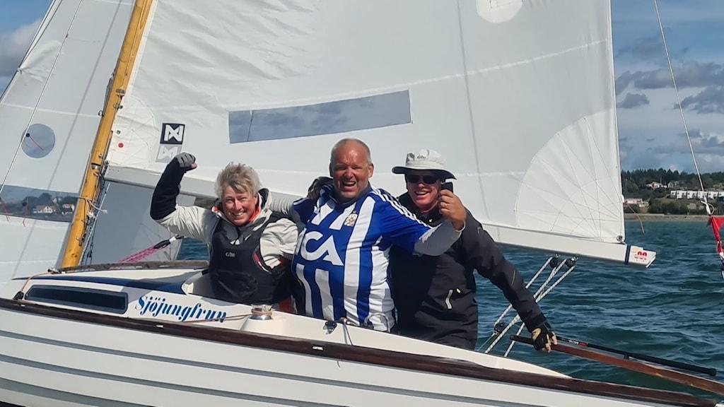 Tre glada personer på en segelbåt, som höjer armarna i en segergest.