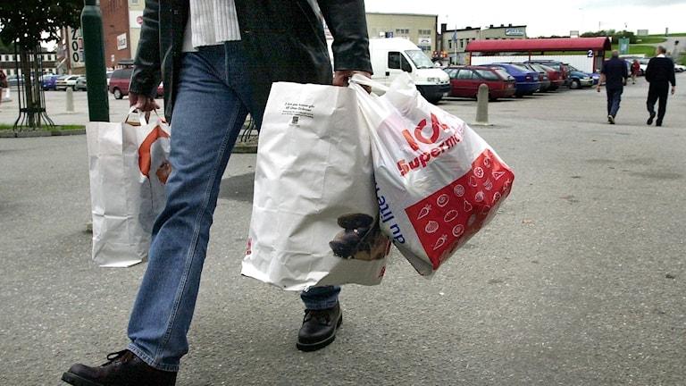 Person bär på flera plastkassar