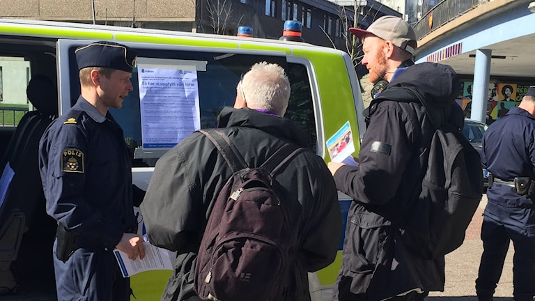 Två män lyssnar på en polis