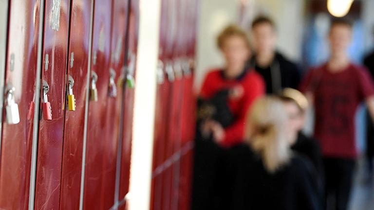 En korridor i en skola. Vid väggen finns elevskåp. I bakgrunden skymtas elever.
