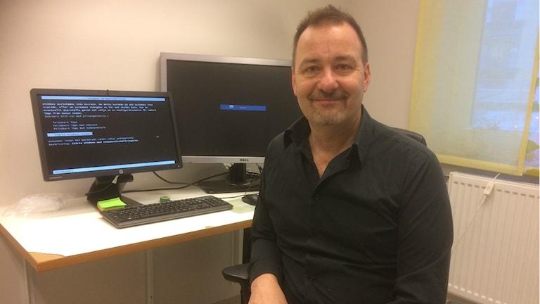En bild på läkaren och forskaren Torsten Olbers. Han sitter framför ett skrivbord med en dator på.