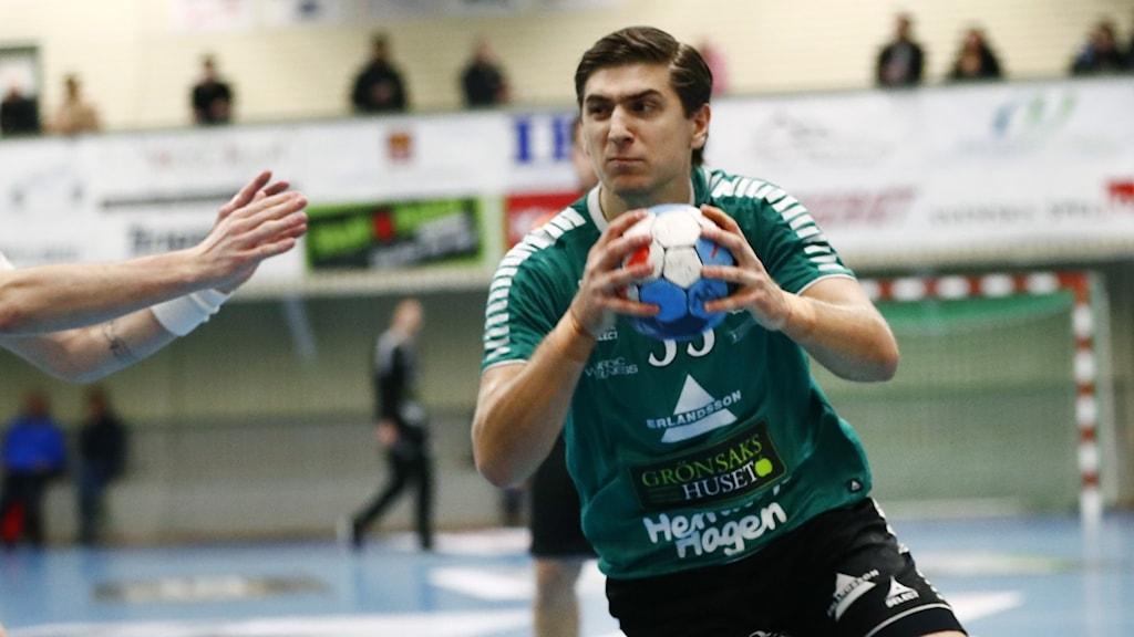 En man med en handboll i händerna.