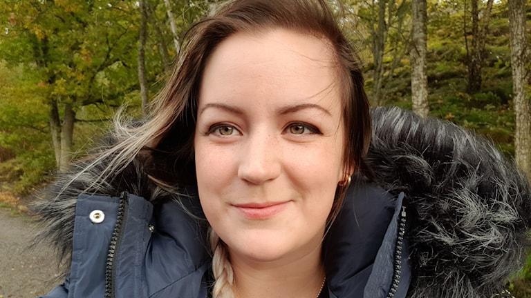 Porträttbild på kvinna med mörkt hår och blå dunjacka.