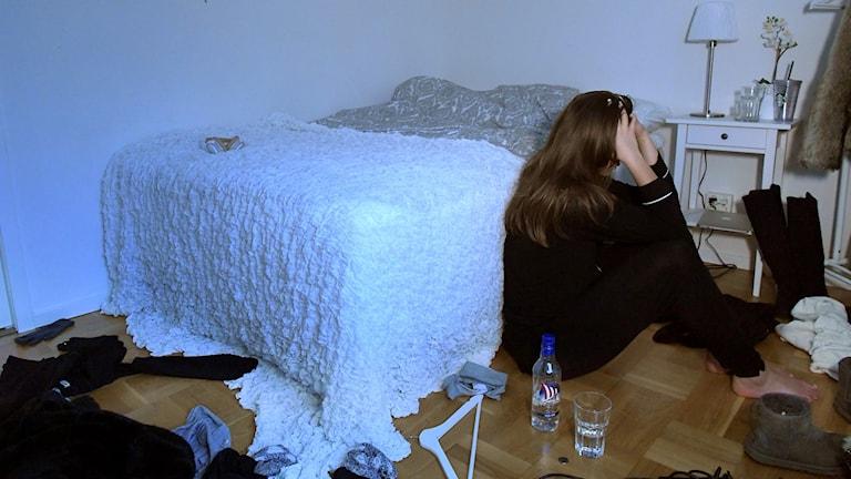 en tonårstjej sitter bredvid sängen berusad med en spritflaska bredvid sig.
