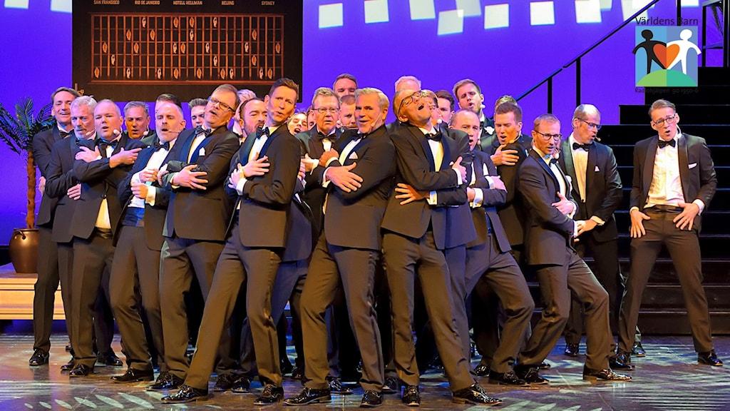 Ett 20-tal män i svarta kostymer showar på en scen.