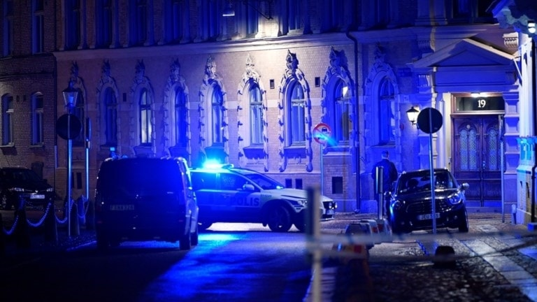 Police cars outside a synagogue at night.